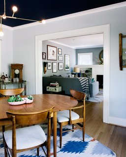 Pull Up a Chair in One of These 20 Modern Dining Rooms - Photo 1 of 20 - A mix of vintage and modern pieces furnish the home, including a table by Arne Vodder for George Tanier, an IKEA rug, and a Lambert & Fils chandelier in the dining room. A bar cart from her grandmother is one of Sarah's most prized possessions. The ceiling color is Benjamin Moore Marine Blue.
