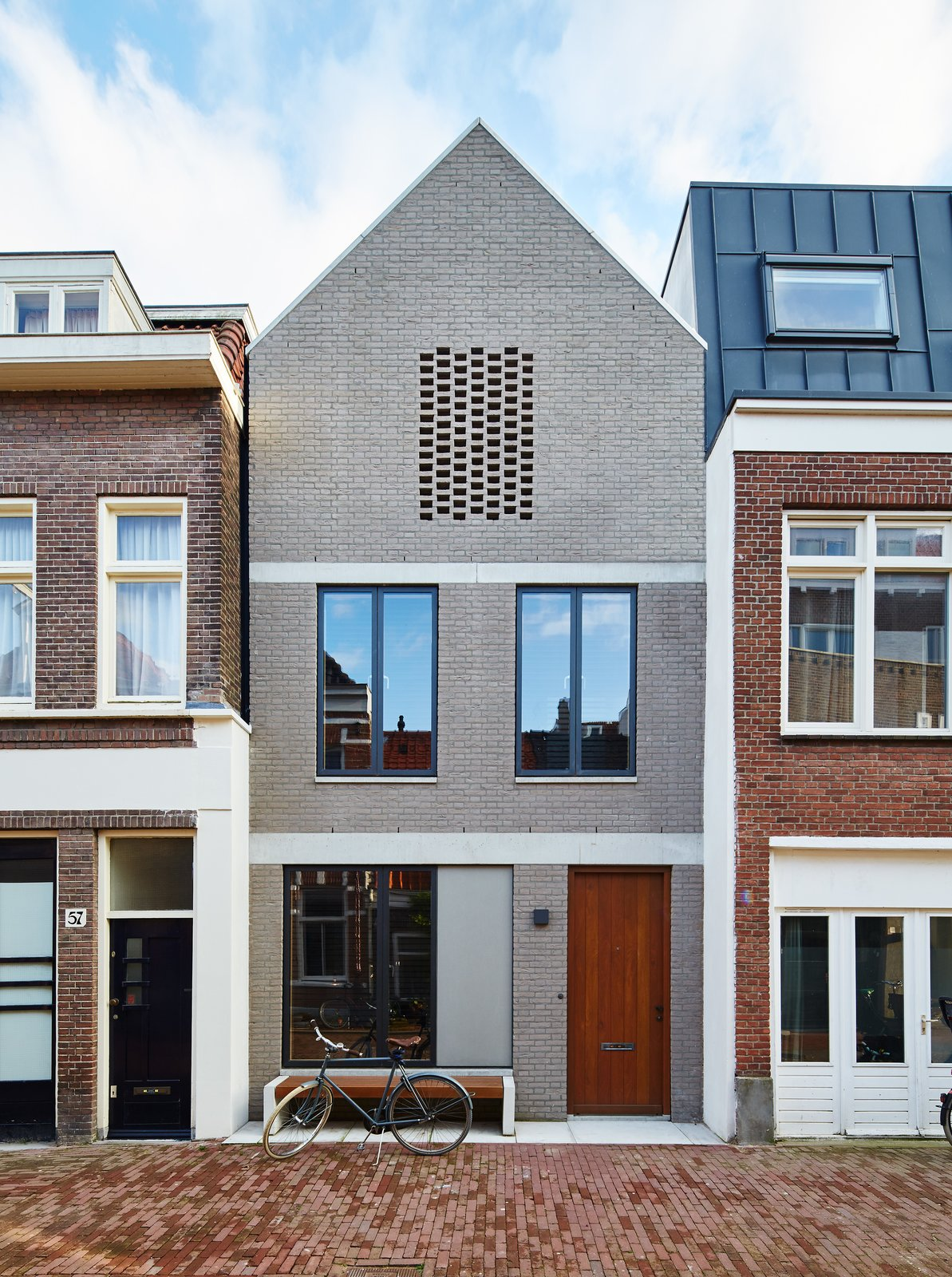 By setting an Amsterdam house a few feet back from the street, 31/44 Architects ensured the city's planning department that the new construction would not block light to the surrounding structures. The gray brick facade references the building material of choice in the formerly industrial neighborhood, which has seen a residential resurgence. Tagged: Exterior, House, Brick Siding Material, and Gable RoofLine.  Photo 2 of 11 in New Kid on the Block