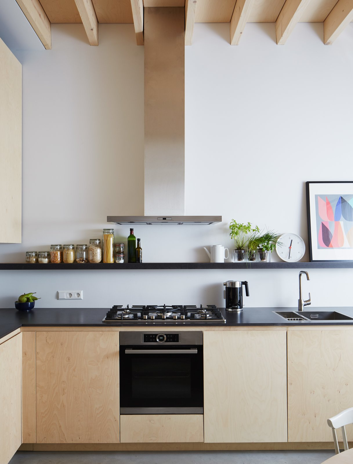The birch plywood cabinets, designed by Jeffries, are paired with engineered wood countertops by Valchromat and appliances by Bosch.