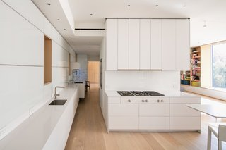 "What's the Twist Behind This Home's Sinuous Staircase? Ordinary Plywood - Photo 4 of 14 - A cooktop and refrigerator from Gaggenau, Bulthaup cabinets, a Miele oven, and an Asko dishwasher outfit the all-white kitchen, which is located onthe entry-level floor. <span style=""line-height: 1.8;"">Recessed Element lights by Tech Lighting provide a minimalist touch.</span>"