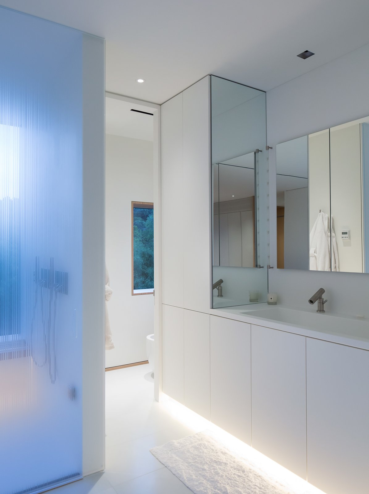 The capacious master suite includes a bathroom with a glass-enclosed shower, under-lit cabinetry, and a box window that looks south toward the garden and pool. The shower fixture and faucet are by Agape. Organic, undulating forms frame the stairwell that connects the first floor and garden floor.