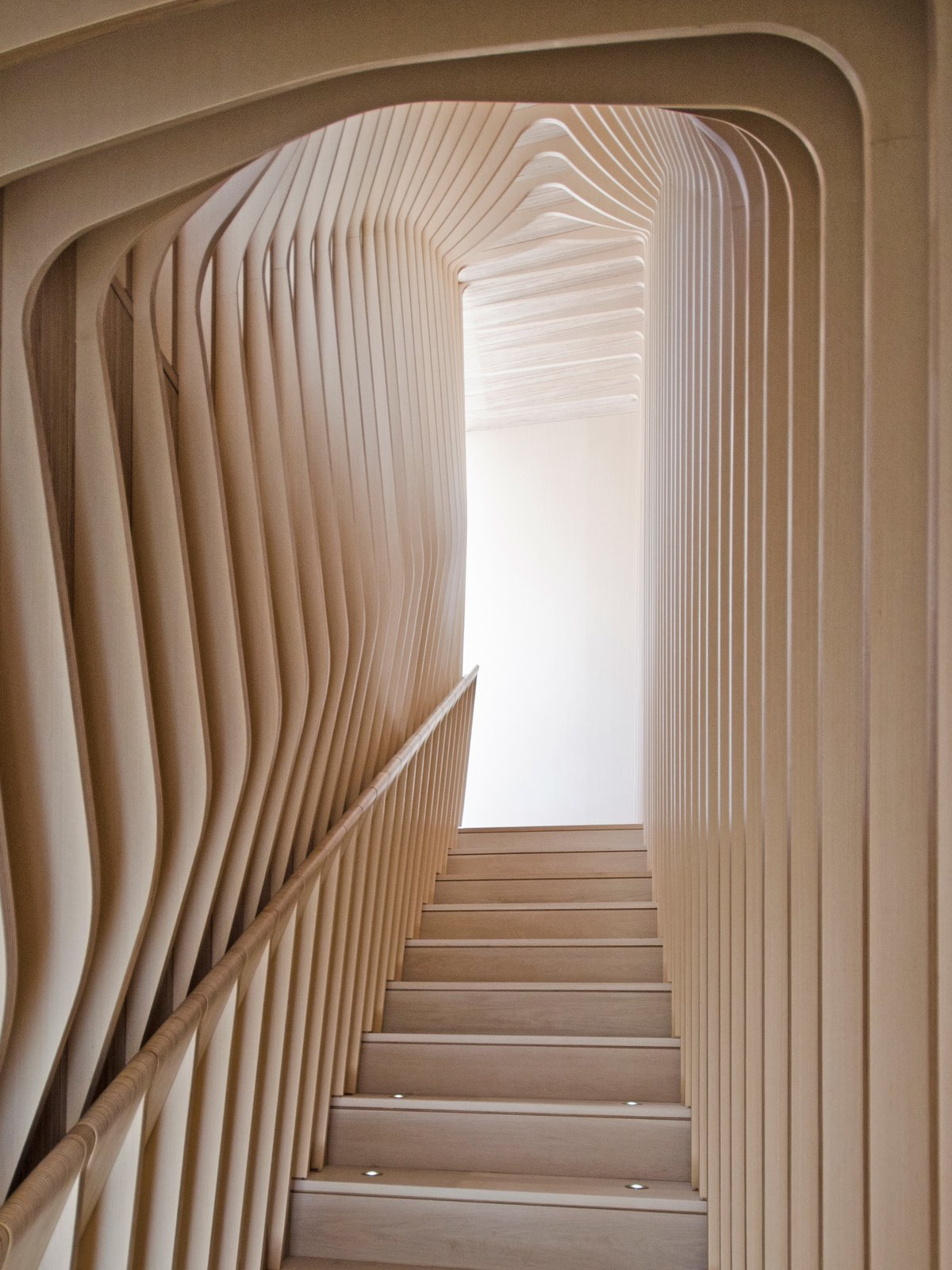 Though they give the appearance of bent plywood, each curved layer of the ribbed corridor was constructed with flat, laminated cutouts, including the rounded hand rail.  Photo 9 of 15 in What's the Twist Behind This Home's Sinuous Staircase? Ordinary Plywood