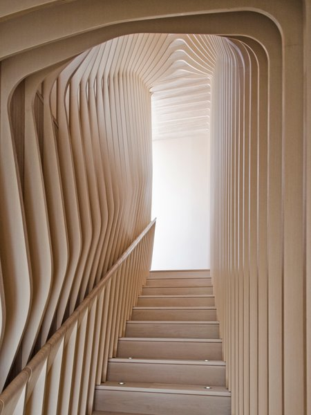 Though they give the appearance of bent plywood, each curved layer of the ribbed corridor was constructed with flat, laminated cutouts, including the rounded hand rail.