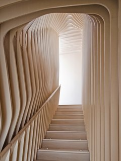 "What's the Twist Behind This Home's Sinuous Staircase? Ordinary Plywood - Photo 8 of 14 - <span style=""line-height: 1.8;"">Organic, undulating forms frame the stairwell that connects the first floor and garden floor. </span>Though they give the appearance of bent plywood, each curved layer of the ribbed corridor was constructed with flat, laminated cutouts, including the rounded hand rail."