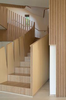 "What's the Twist Behind This Home's Sinuous Staircase? Ordinary Plywood - Photo 9 of 14 - <span style=""line-height: 1.8;"">A view of the central staircase from the entry-level floor emphasizes vertical, tapering forms, a motif found throughout the home.</span>"