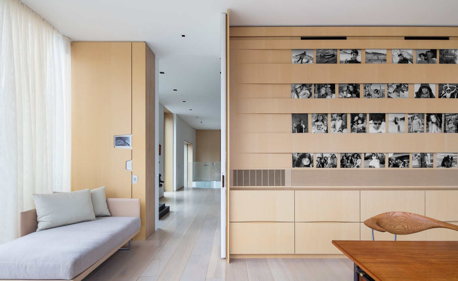 The husband's home office is furnished by a Toot lounge chair by Piero Lissoni for Cassina, a vintage Desk BO69 by Finn Juhl, and a Swivel chair by Hans Wegner. A custom picture rail, filled with family photos, is made of bands of wood that keep contents in place.  Photo 11 of 15 in What's the Twist Behind This Home's Sinuous Staircase? Ordinary Plywood