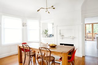 Check Back - Photo 3 of 14 - Three furniture icons, in pairs, surround the dining room table: the Eames Side, Thonet No. 14, and Peter Opsvik Tripp Trapp chairs. Cheng and Snyder customized the pendant using components from Lindsey Adelman's DIY collection. The walls now match the white fireplace, one of the original features preserved during the renovation.