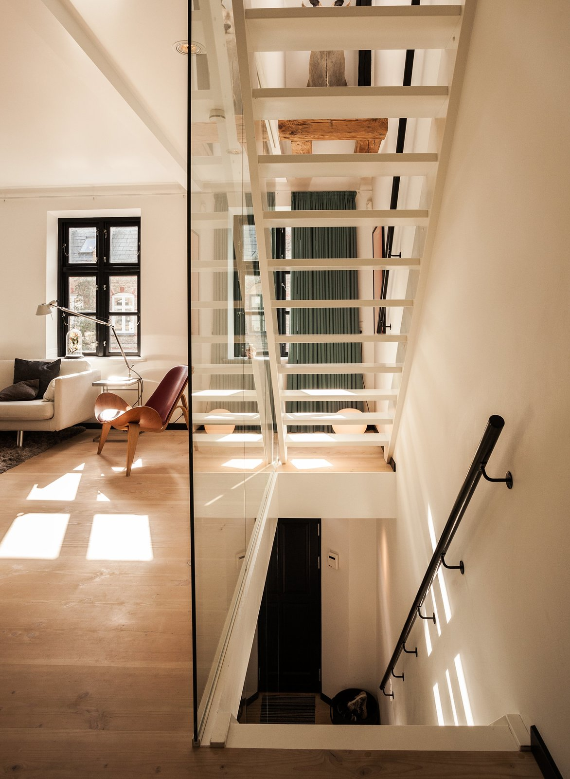 """""""From the day we got our house, I knew exactly how I wanted it done,"""" says Mia Dalgas, who led the renovation of her family's 1880s home in Copenhagen's Potato Rows district. One of the biggest transformations was the addition of a glass-enclosed lacquered wood staircase.  Photo 2 of 8 in Urban Renewal"""