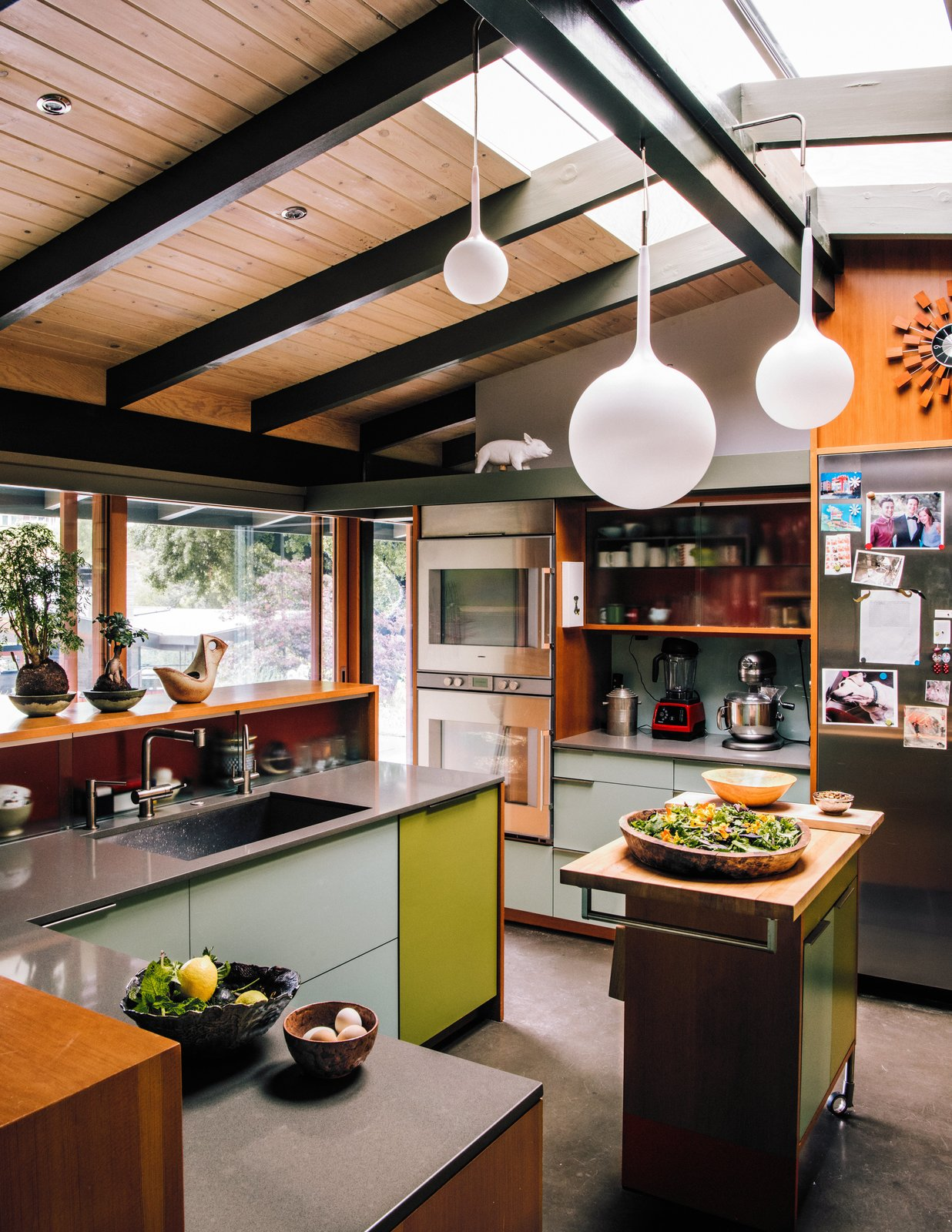 Tagged: Kitchen, Undermount Sink, Wall Oven, Cooktops, Refrigerator, Wood Counter, Colorful Cabinet, Concrete Floor, Ceiling Lighting, and Pendant Lighting.  Photo 2 of 14 in Creative Revival of a Modernist Gem