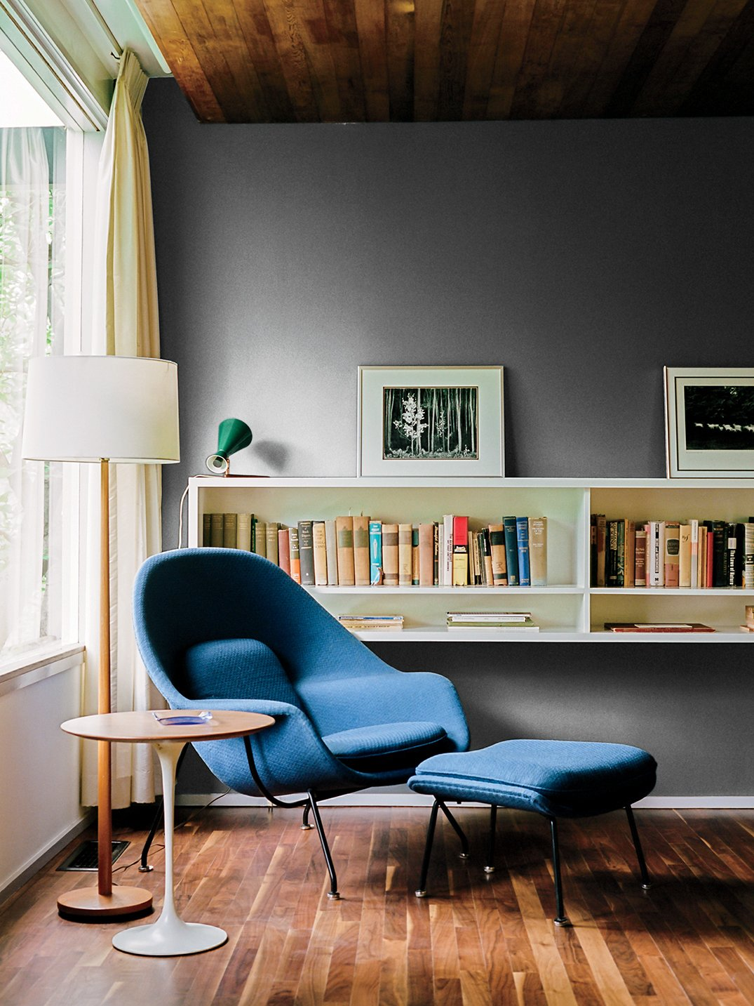 A walnut-topped table and Womb chair, both by Eero Saarinen for Knoll, offer a cozy spot for reading. Tagged: Living Room, Floor Lighting, Medium Hardwood Floor, Bookcase, Ottomans, Storage, Shelves, and End Tables.  47+ Midcentury Modern Homes Across America by Luke Hopping from Kansas City Royal