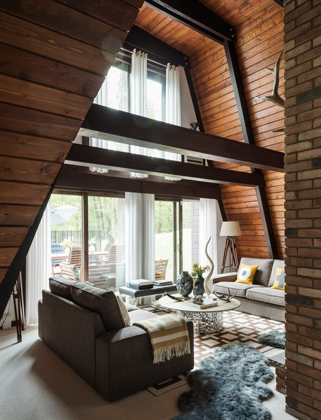 Original tongue-and-groove pine boards, restained a warm chestnut hue, run horizontally to the ceiling. The residents layered gray sheepskin rugs on top of wool berber carpeting, installed by Joseph Velletri's Sons.
