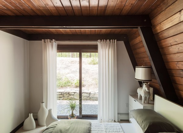 The guest bedrooms feature lighting by Jonathan Adler, including a Horse table lamp in the downstairs unit and an Antwerp pendant upstairs.
