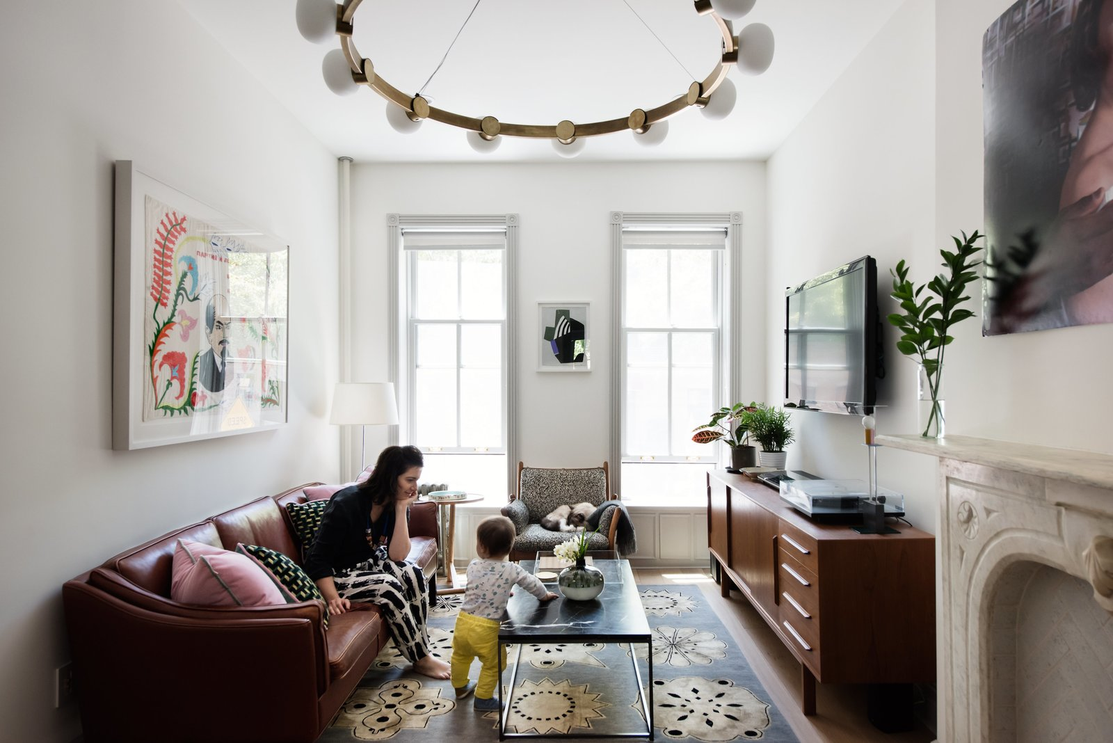 Interior designer Merrill Lyons plays with her son in the Brooklyn home she renovated with her husband, Charles Brill, a lighting designer and cofounder of New York–based company Rich Brilliant Willing (RBW). The couple's design sensibility is marked by a warm mix of historic periods and styles, punctuated with pieces by RBW, including the circular brass Cinema chandelier that hangs in the living room. The leather sofa and teak  credenza are vintage; the 1960s rosewood Genius armchair by Danish designer Illum Wikkelso was reupholstered with fabric sourced from an outlet. Tagged: Living Room, Sofa, Pendant Lighting, Ceiling Lighting, Table Lighting, Console Tables, End Tables, Coffee Tables, Lamps, Rug Floor, and Light Hardwood Floor.  Photo 5 of 9 in 6 Main Tips to Consider When Designing Your Home For a Growing Family from Modern Becomes Eclectic in This Renovated Brooklyn Townhouse