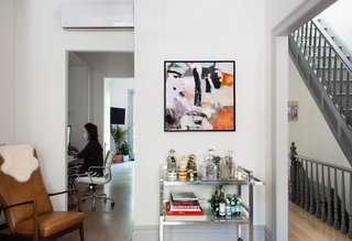 Modern Becomes Eclectic in This Renovated Brooklyn Townhouse - Photo 2 of 13 - Lyons works in her home office sited between the kitchen and the living room. A 1970s chrome bar cart stocked with vintage decanters sits near a leather-and-teak armchair by mid-century Danish designer Søren J. Ladefoged that Lyons inherited from her family.