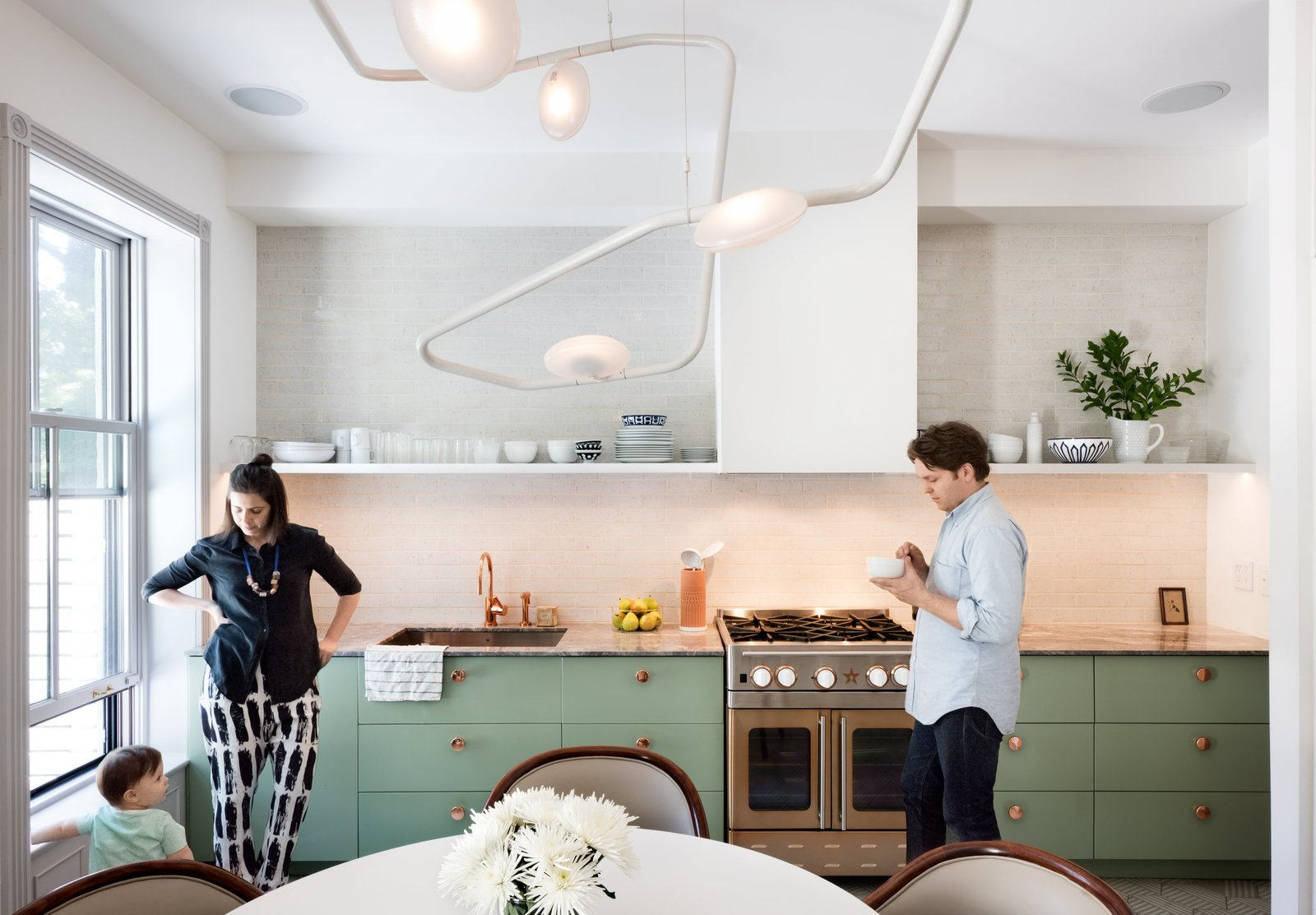 The couple's bold mix-and-match sensibility applies most unconventionally to the material palette; nearly every surface is different from the next. The cook station pairs a copper Watermark faucet with an Italian marble countertop, a copper-toned stainless-steel range from Blue Star, and a backsplash of masonry Foundation Brick tile by Ann Sacks. Tagged: Kitchen, Colorful, Pendant, Range, and Undermount.  Best Kitchen Pendant Colorful Photos from Modern Becomes Eclectic in This Renovated Brooklyn Townhouse