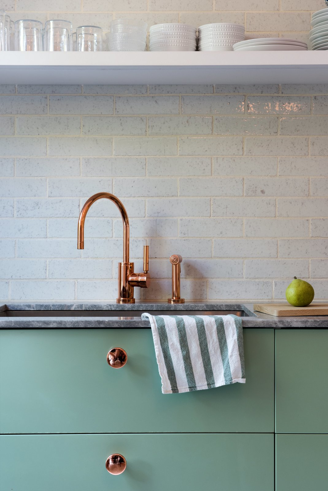 Lyons and Brill designed several custom touches, like the copper-plated knobs they installed on the Sektion kitchen cabinetry from IKEA, painted in Farrow & Ball's muted Breakfast Room Green. Tagged: Kitchen, Undermount Sink, and Marble Counter.  Photo 7 of 14 in Modern Becomes Eclectic in This Renovated Brooklyn Townhouse