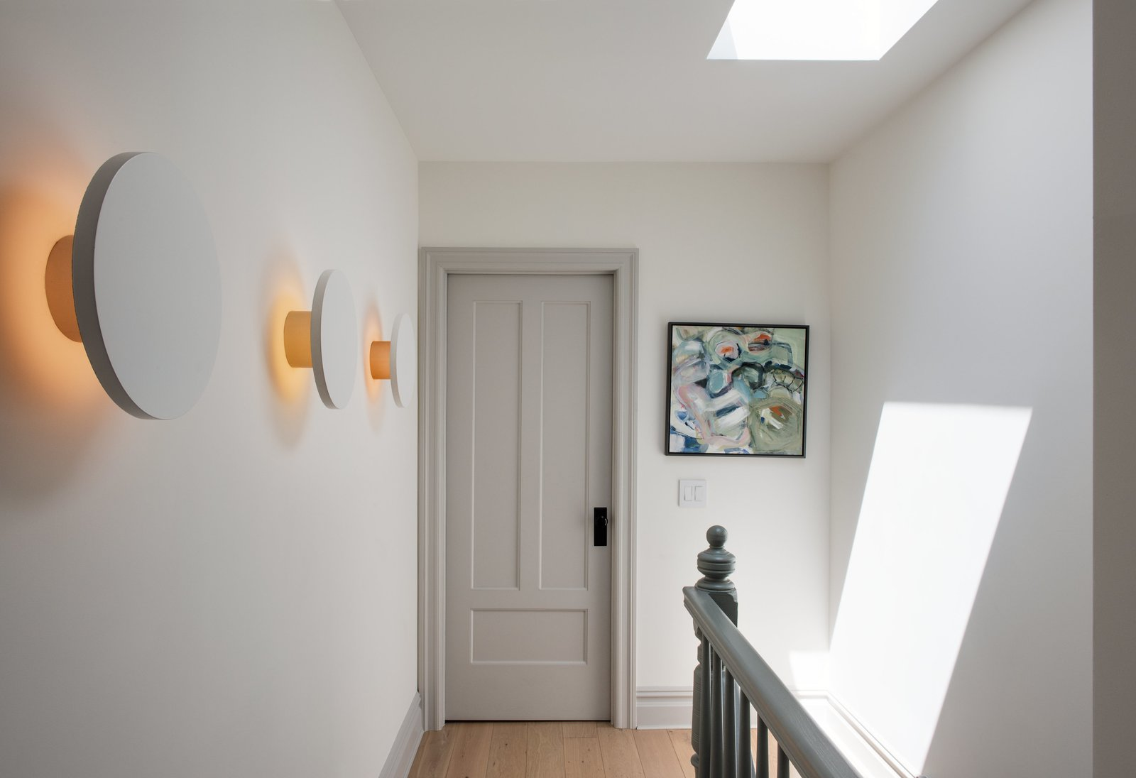 A series of Radient sconces by RBW illuminates the third-floor landing with a subtle graphic pop. Tagged: Hallway and Light Hardwood Floor.  Photo 8 of 14 in Modern Becomes Eclectic in This Renovated Brooklyn Townhouse