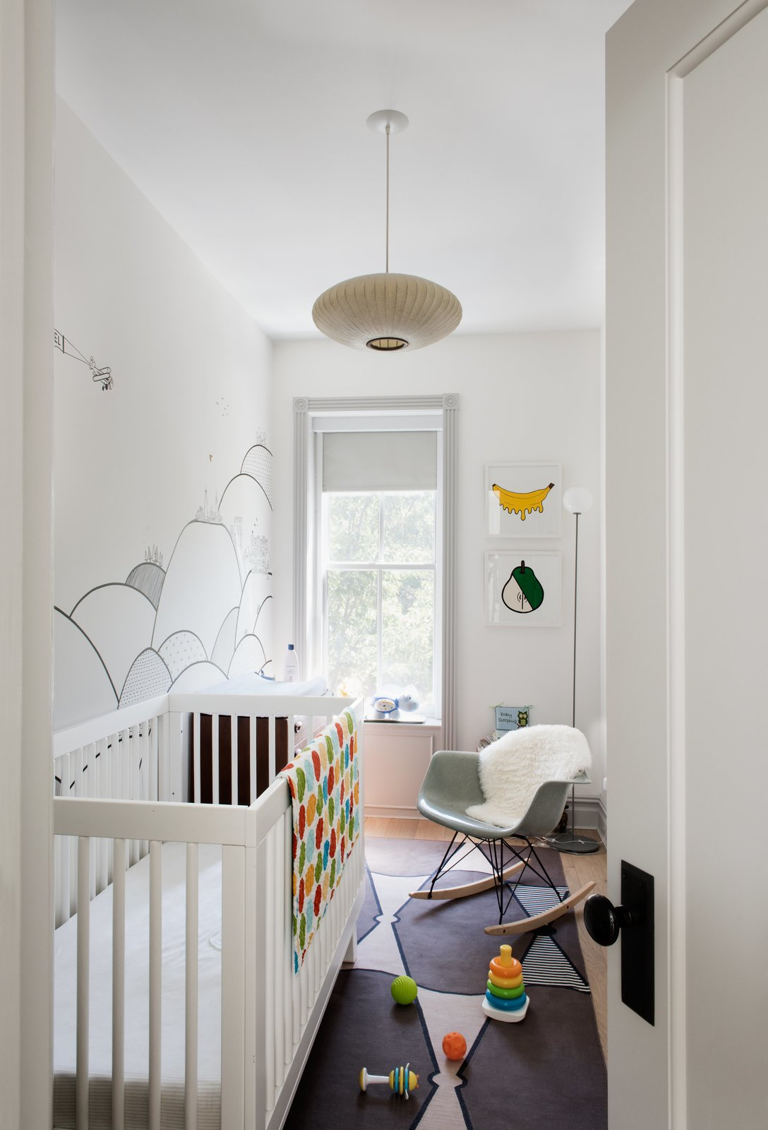 A mural by local illustrator Kale Williams—a good friend and the wife of one of Brill's partners—provides the backdrop forthe nursery. Tagged: Kids Room, Bedroom, Bed, Rockers, Medium Hardwood Floor, Toddler Age, and Neutral Gender.  Photo 10 of 14 in Modern Becomes Eclectic in This Renovated Brooklyn Townhouse