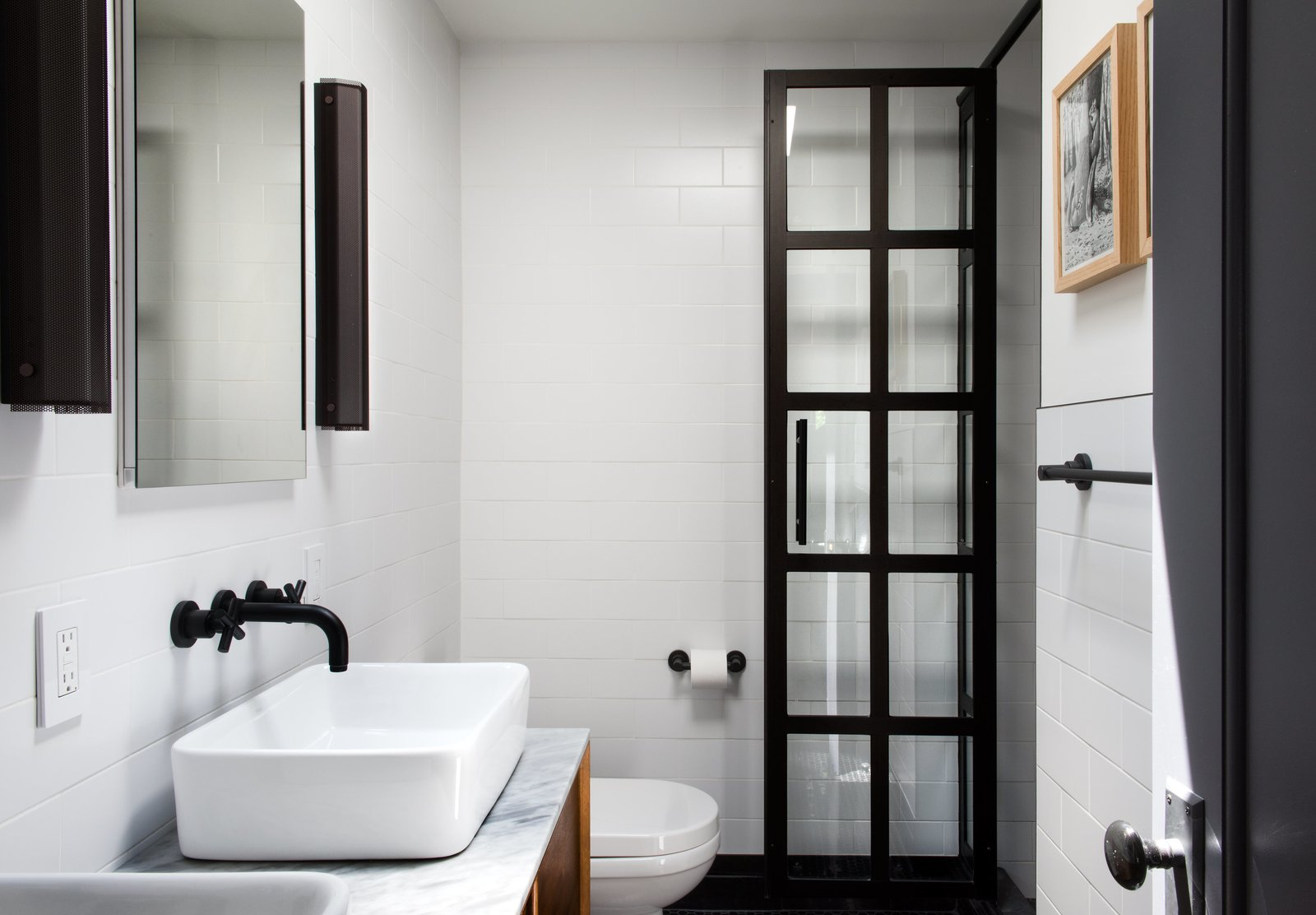 An austere palette defines the master bathroom, with subway tiles from Classic Tile New York, matte-black fixtures by California Faucets, and black perforated-aluminum Branch sconces by RBW. Tagged: Bath Room, Marble Counter, Vessel Sink, and Subway Tile Wall.  Photo 11 of 14 in Modern Becomes Eclectic in This Renovated Brooklyn Townhouse