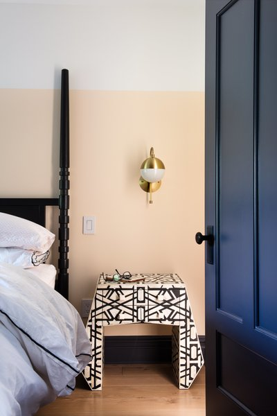 In the master bedroom, expanses of white and peach paint play against the geometric lines of an inlaid-bone nightstand from Anthropologie. The traditional four-poster bed is from West Elm; the brass Cedar & Moss sconce is from Rejuvenation.