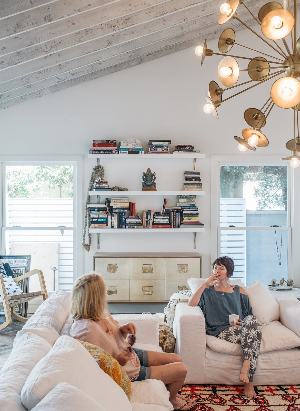 Actress Lena Headey (with her mother, Susan) worked with builder Ted Broden to give her 1950s house an open feel. The living room includes a Cloud Track Arm sofa and chair from Restoration Hardware, a Woven Accents rug, and a Keegan chandelier by Arteriors.