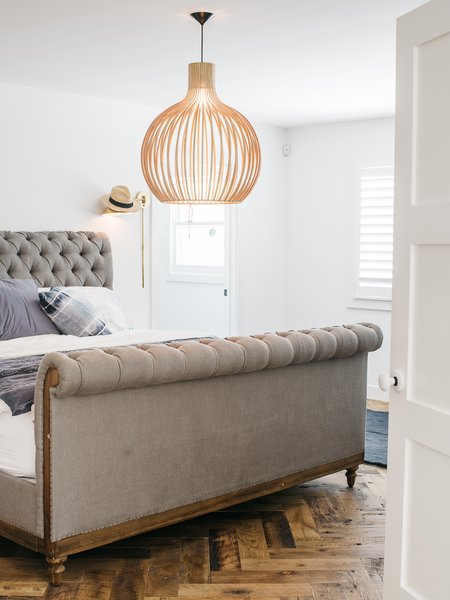 "Adding a partial second floor accommodated bedrooms for Lena; her son, Wylie; and her daughter, Teddy. The master bedroom features a Chesterfield bed from Restoration Hardware and a pendant by Seppo Koho. ""I saw tons of houses that were done and a few that needed redoing,"" says Lena. ""This one was small, but it made sense."""