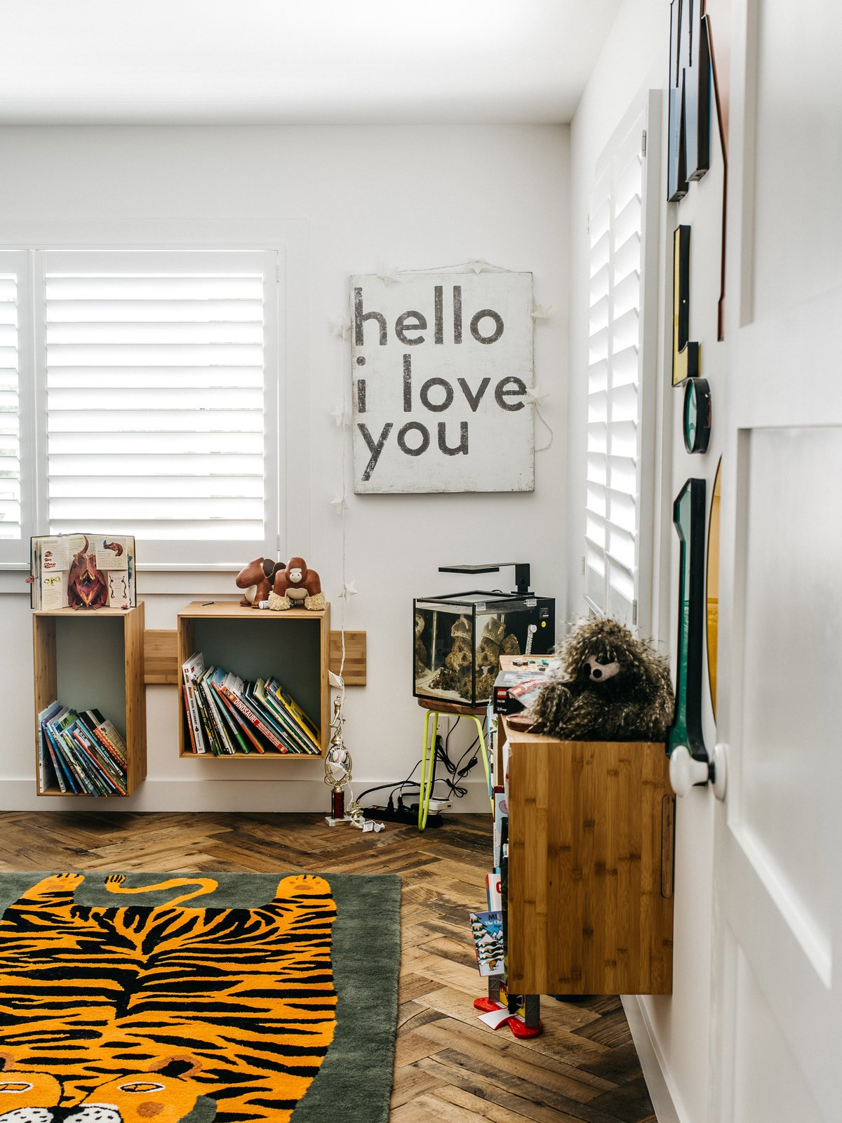 """Wylie's bedroom features a rug from the Land of Nod and a sign from a local shop. """"I put the shelves up myself on my seventh attempt,"""" Lena says. """"If I move them, I guarantee you'll see nineteen holes."""""""