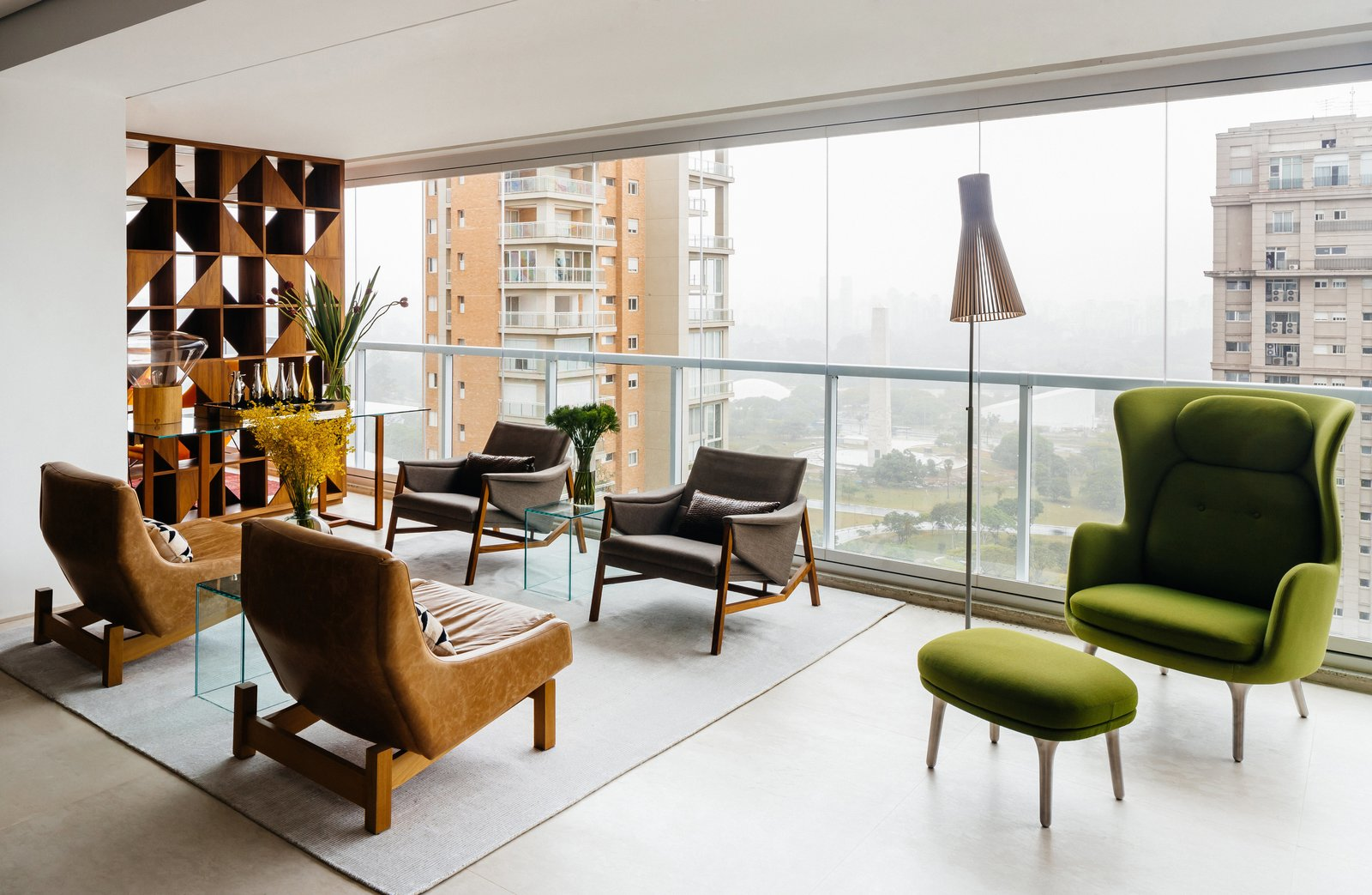 In an apartment overlooking São Paulo's Ibirapuera Park—completed in 1954 to commemorate the city's 400th anniversary—the furniture is as distinctive as the view. Architect Flavio Castro of FCstudio worked closely with the residents to update and outfit the home, which is appointed with a mix of contemporary and Brazilian modern classics. A pair of Sérgio Rodrigues's Paraty armchairs (in foreground)—designed for Brasilia's Itamaraty Palace in 1963—face a duo of Jader Almeida's Isa armchairs in the living area. The green Ro lounge and ottoman are by Jaime Hayon for Fritz Hansen.  Photo 1 of 9 in Overlooking a Niemeyer Masterpiece, This Flat is Filled with Brazilian Modern Gems