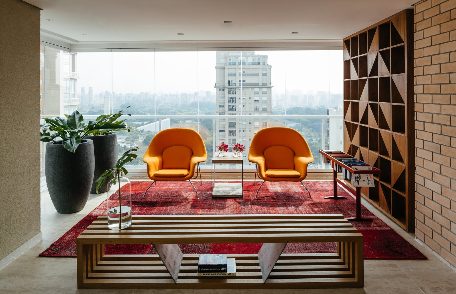 Two Womb chairs by Eero Saarinen for Knoll and a Ring bench by Castro structure a reading area in the enclosed terrace.  Photo 2 of 9 in Overlooking a Niemeyer Masterpiece, This Flat is Filled with Brazilian Modern Gems