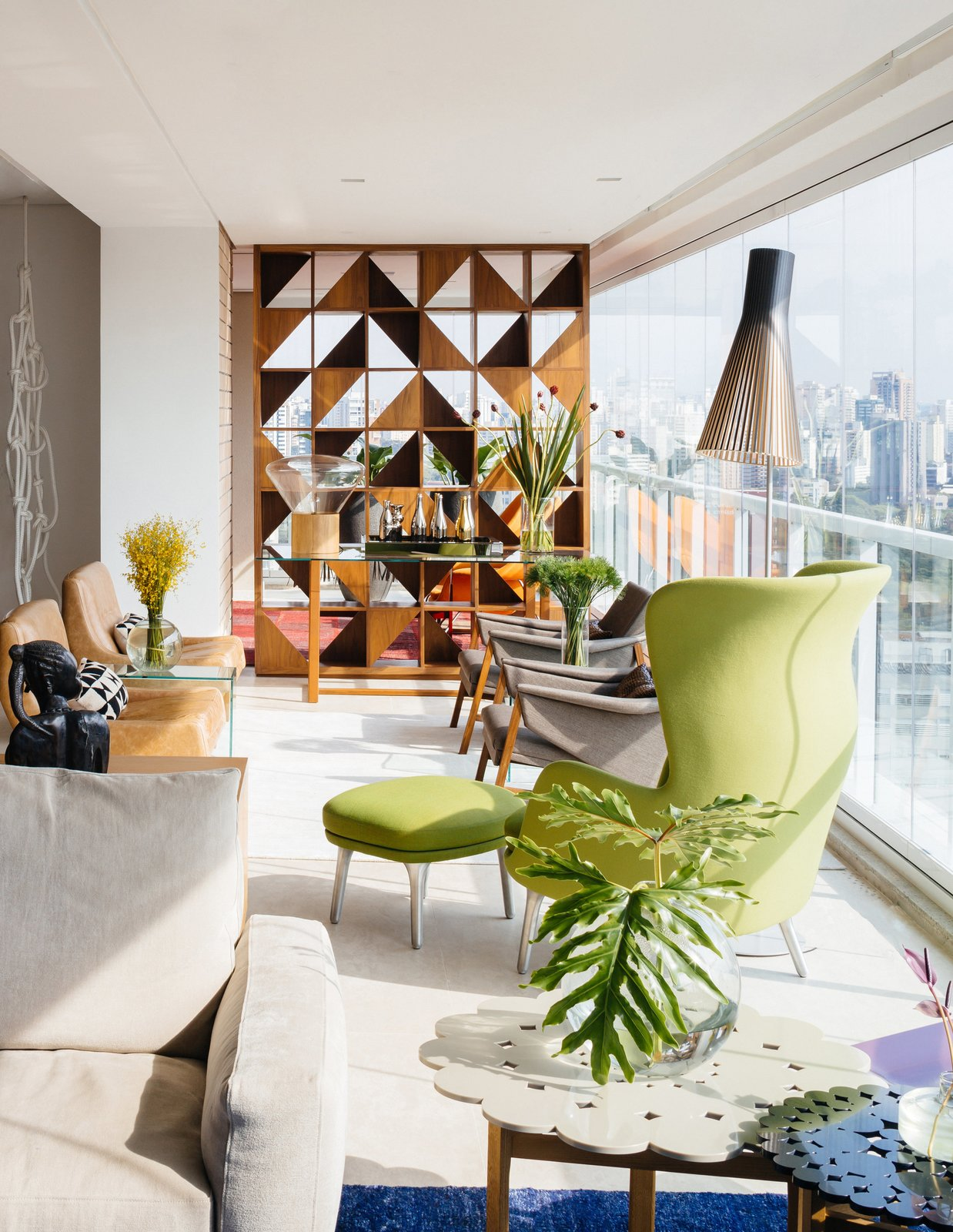FCstudio updated the 5,000-square-foot apartment by removing several walls in central areas to clarify views and simplify the overall floor plan. The firm also custom-designed the Brazilian walnut room divider with a striking geometric pattern that allows light to traverse throughout the living area. Tagged: Living Room, Chair, Sofa, Recliner, Coffee Tables, End Tables, Lamps, Ceiling Lighting, Rug Floor, Recessed Lighting, and Floor Lighting.  Photo 3 of 9 in Overlooking a Niemeyer Masterpiece, This Flat is Filled with Brazilian Modern Gems