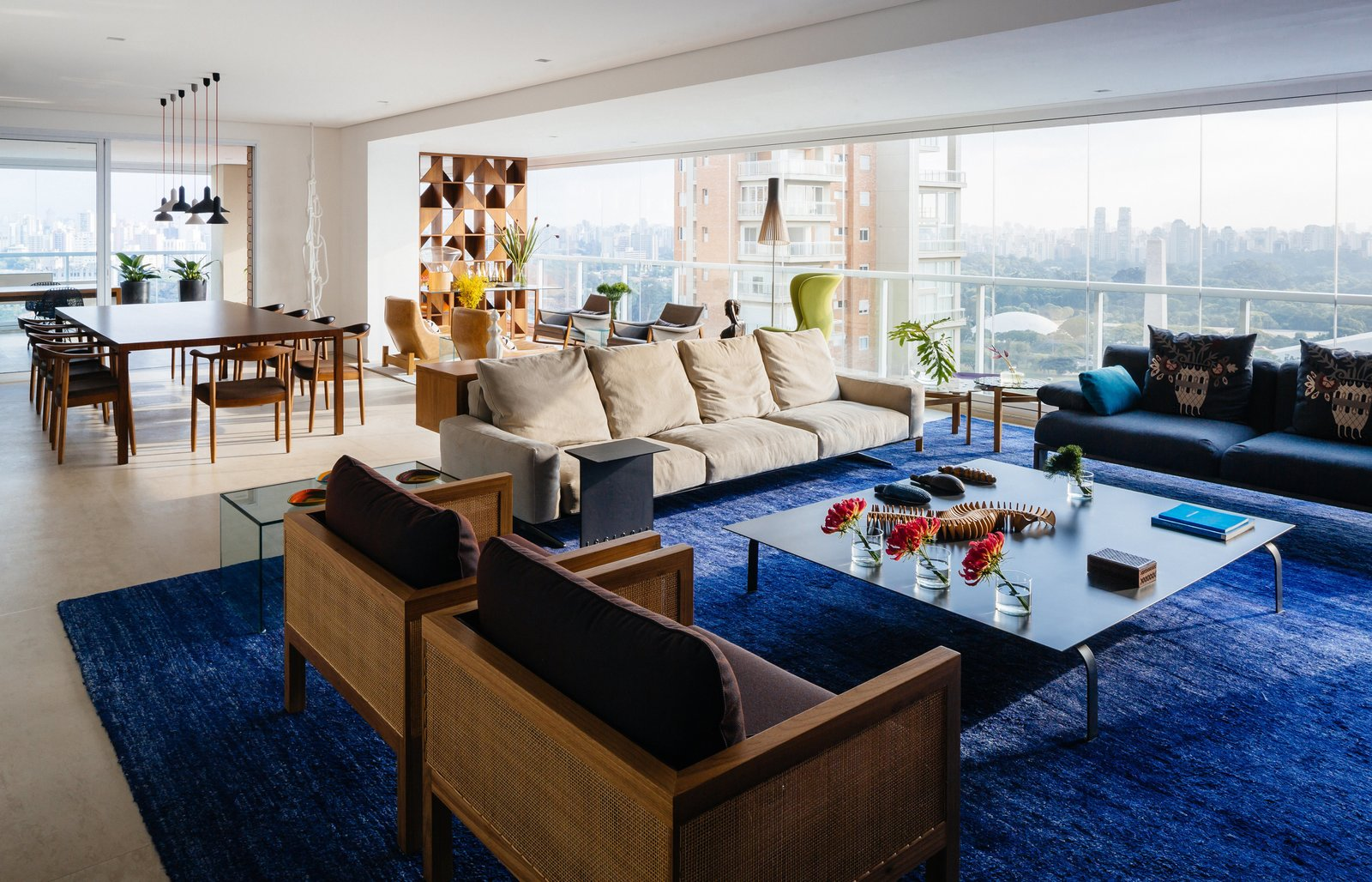 Furniture groupings and bright, dramatic accents—like the sapphire banana-fiber rug by Kamy Maison in the main living area—further divide the interior into distinct yet flexible stations. The trio of seating options includes wood-and-cane Cosme Velho armchairs by Claudia Moreira Salles, a plush Soft Dream leather sofa by Antonio Citterio for Flexform, and a blue Fergana sofa by Patricia Urquiola for Moroso. Just beyond, a Fina table, also by Salles, joins Marta chairs by Aristeu Pires and Torch pendants by Sylvain Willenz to form the dining area. Tagged: Living Room, Bench, Sofa, Recliner, End Tables, Coffee Tables, Sectional, Chair, Lamps, Floor Lighting, Ceiling Lighting, Recessed Lighting, Pendant Lighting, and Rug Floor.  Photo 4 of 9 in Overlooking a Niemeyer Masterpiece, This Flat is Filled with Brazilian Modern Gems