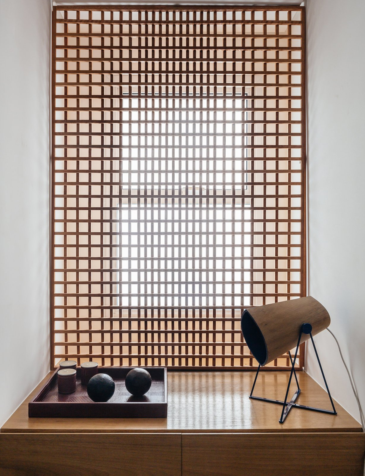 FCstudio designed the gridded Muxarabi panel made of catuaba wood; placed in front of the home office window, it softens light to a diffuse glow. Tagged: Living Room, Storage, Lamps, and Table Lighting.  Photo 7 of 9 in Overlooking a Niemeyer Masterpiece, This Flat is Filled with Brazilian Modern Gems