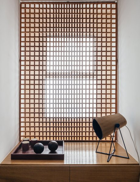 FCstudio designed the gridded Muxarabi panel made of catuaba wood; placed in front of the home office window, it softens light to a diffuse glow. Tagged: Storage.  Photo 7 of 9 in Overlooking a Niemeyer Masterpiece, This Flat is Filled with Brazilian Modern Gems