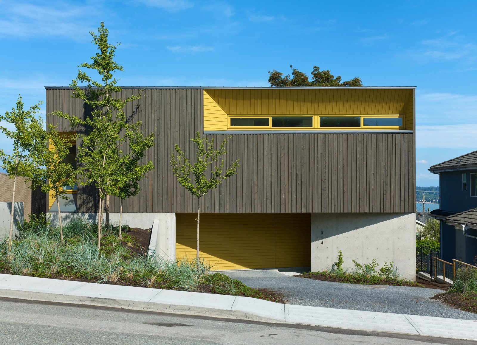 The exterior is clad in stained cedar and painted channel siding; the Turmeric shade was selected to complement the hue of the ginkgo trees in the front yard.