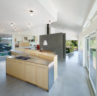 A Suburban Vancouver Home Edits its Privacy Settings - Photo 3 of 5 - The kitchen includes custom ash cabinets made by JMV Woodworks paired with stainless-steel countertops.