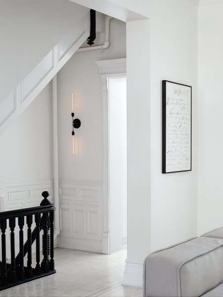 After restoring and renovating the interior of their four-story brownstone in Brooklyn's Bedford-Stuyvesant neighborhood, Jeff Madalena and Jason Gnewikow—creative entrepreneurs and self-described interiors obsessives—outfitted the historic 1910 space with a minimal black-and-white palette, down to the stair railing and original moulding and wainscoting. Sparse, modern pieces—like a two-pronged sconce they designed for the parlor-floor landing and a Cy Twombly print in the adjacent family room—provide elegant counterpoints to the architecture.