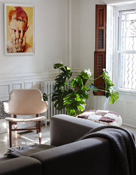 A Prostoria Match sofa from Cite pairs with a vintage armchair and a Ryan McGinley print in the family room on the garden floor.