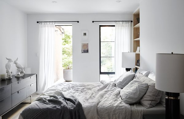 Antique Art Deco–style lamps flank a West Elm bed in the master bedroom, which accesses a private backyard garden. The smoke-colored Series 11 6 Drawer Console is from Blu Dot; the built-in shelving was custom-made by Wood Management.
