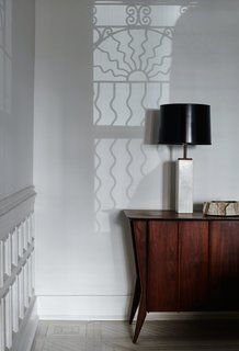 Graphic, curvilinear shadows cast from an original window grate play with geometrically stark furnishings, including the vintage lamp and midcentury Danish credenza in the family room.