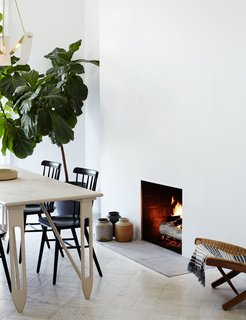 A Fashionable Couple Remake Their Brooklyn Brownstone with a Sartorial Twist - Photo 6 of 10 - Shaker-style Salt chairs by Tom Kelley join a custom-sized Etoile dining table and Tsuru Flush Mount III pendant, both by Materia Designs. The couple removed an ornamental fireplace mantel in the kitchen, one of few period details they decided not to keep, due to its size.