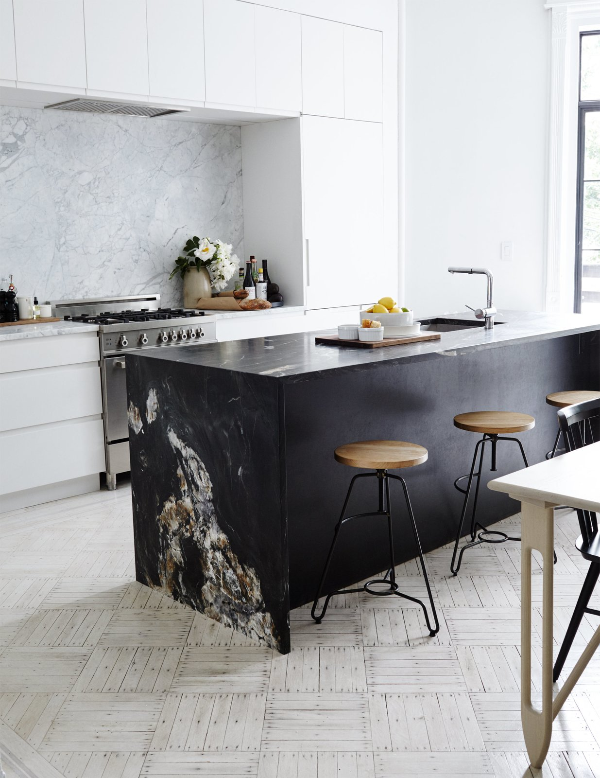 The couple removed an ornamental fireplace mantle in the kitchen, one of few period details they decided not to keep, due to its size. Matte-black quartzite slabs from ABC Worldwide Stone form the kitchen island, which is outfitted with Blanco fixtures; a white Carrara backsplash frames the Bertazzoni range and Dunsmuir cabinetry. The oak-and-steel bar stools are from ABC Carpet & Home. Tagged: Kitchen, White Cabinet, Marble Counter, Marble Backsplashe, and Range.  Kitchen by Lara Deam from A Fashionable Couple Remake Their Brooklyn Brownstone with a Sartorial Twist