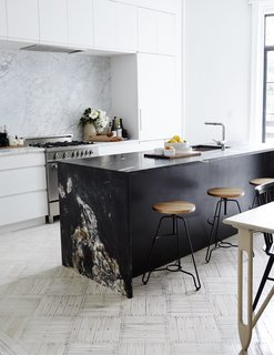 Matte-black quartzite slabs from ABC Worldwide Stone form the kitchen island, which is outfitted with Blanco fixtures; a white Carrara backsplash frames the Bertazzoni range and Dunsmuir cabinetry. The oak-and-steel bar stools are from ABC Carpet & Home.