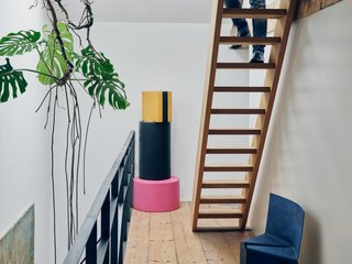 Futuristic Forms Meet Historical Details in Designer Danny Venlet's Brussels Home - Photo 2 of 11 - A stack of foam poufs from Venlet's colorful, candy-inspired Let's Drop collection joins his blue, powder-coated Cake chair on the third-floor landing.