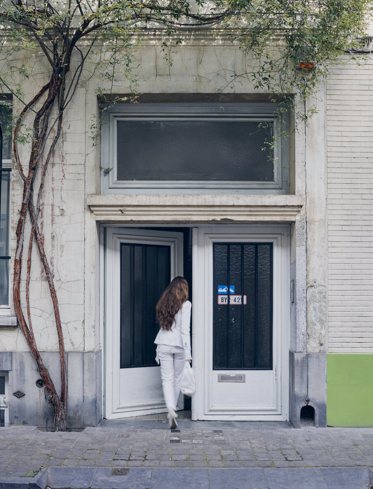 Venlet's wife and business partner, Evi Lippens, enters the home's unassuming street entrance in the city's Flemish Dansaert district.  Photo 6 of 11 in Futuristic Forms Meet Historical Details in Designer Danny Venlet's Brussels Home