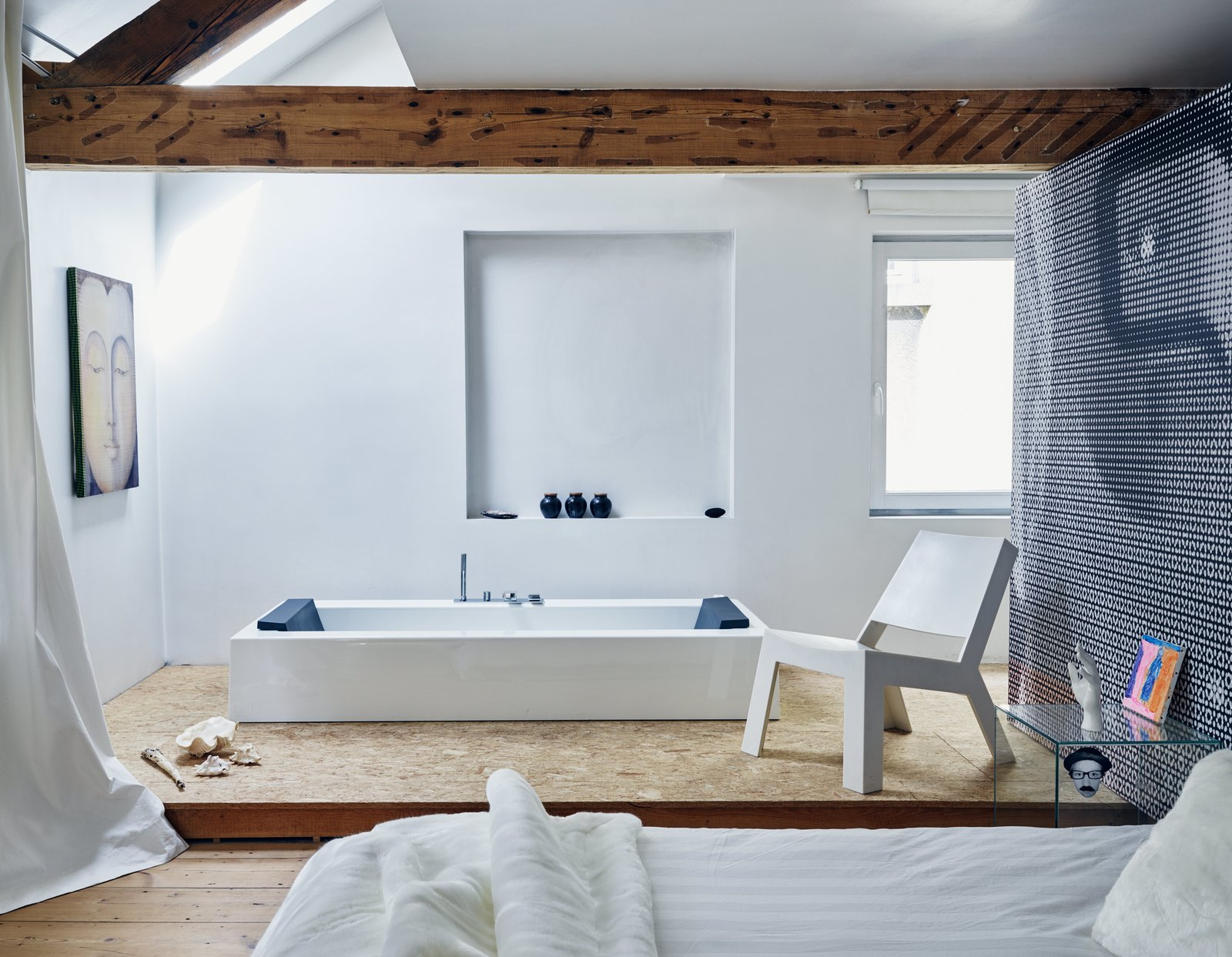 A spare layout marks the master suite on the third floor. The rectangular KOS bathtub, integrated into an elevated plywood platform, pairs with Gert Van Der Vloet's Cut Low lounge in Corian. The couple used elements of a photo they took of one of Venlet's designs to create the graphic wall covering.  Tagged: Bath Room, Soaking Tub, and Light Hardwood Floor.  Photo 8 of 11 in Futuristic Forms Meet Historical Details in Designer Danny Venlet's Brussels Home