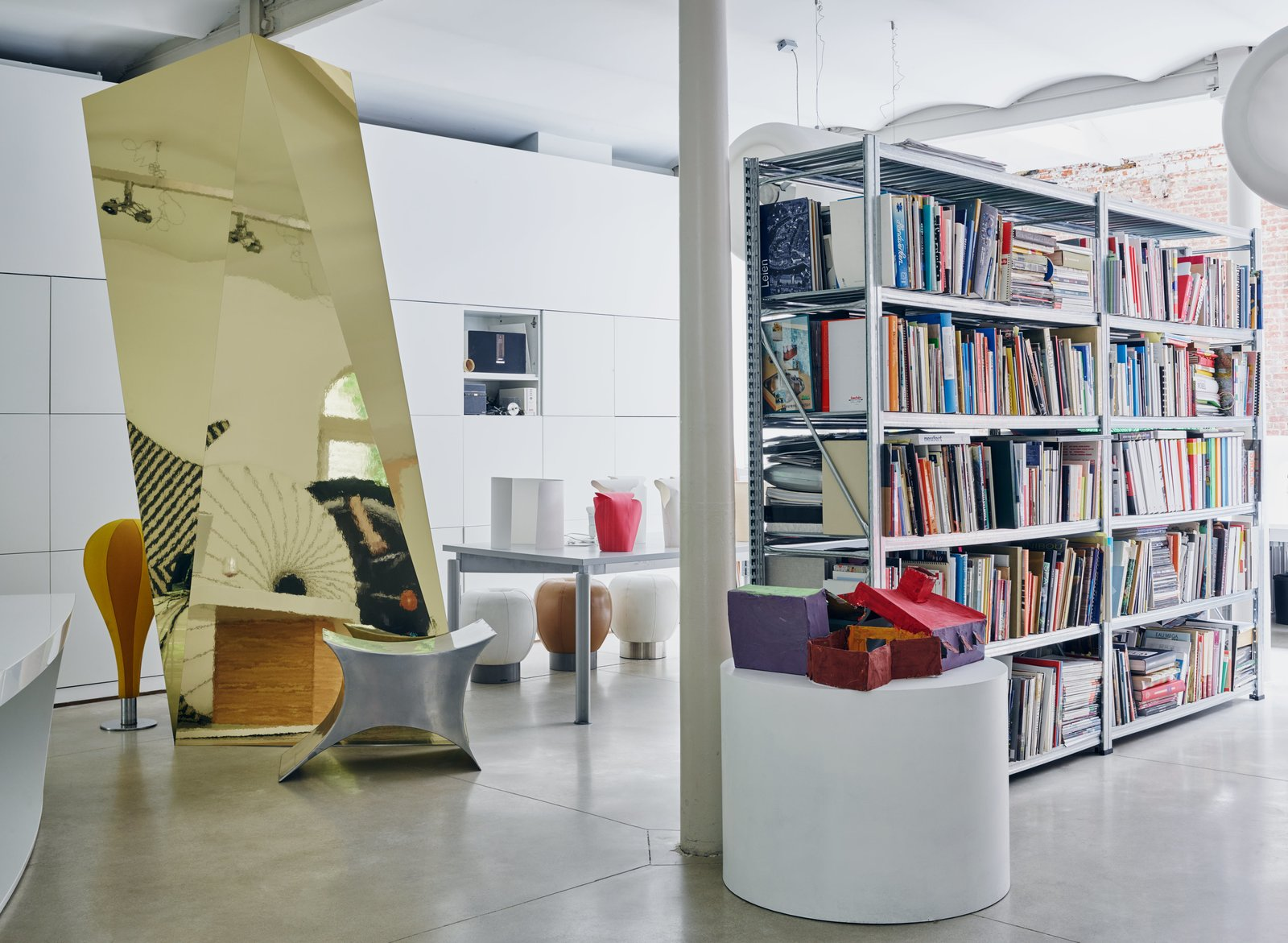 Books, models, and more prototypes—including the 1991 Powder Horse stool, composed of concave stainless-steel surfaces—fill Venlet's atelier.  Tagged: Storage Room and Shelves Storage Type.  Photo 9 of 11 in Futuristic Forms Meet Historical Details in Designer Danny Venlet's Brussels Home