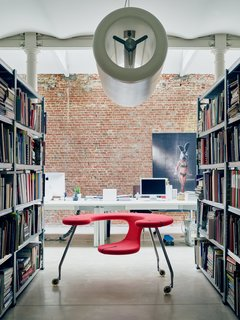 Futuristic Forms Meet Historical Details in Designer Danny Venlet's Brussels Home - Photo 10 of 11 - Recalling the form of an airplane engine, his cylindrical D2V2 pendant hovers above his sculptural Easy Rider, a mobile desk-seat hybrid set on castors.