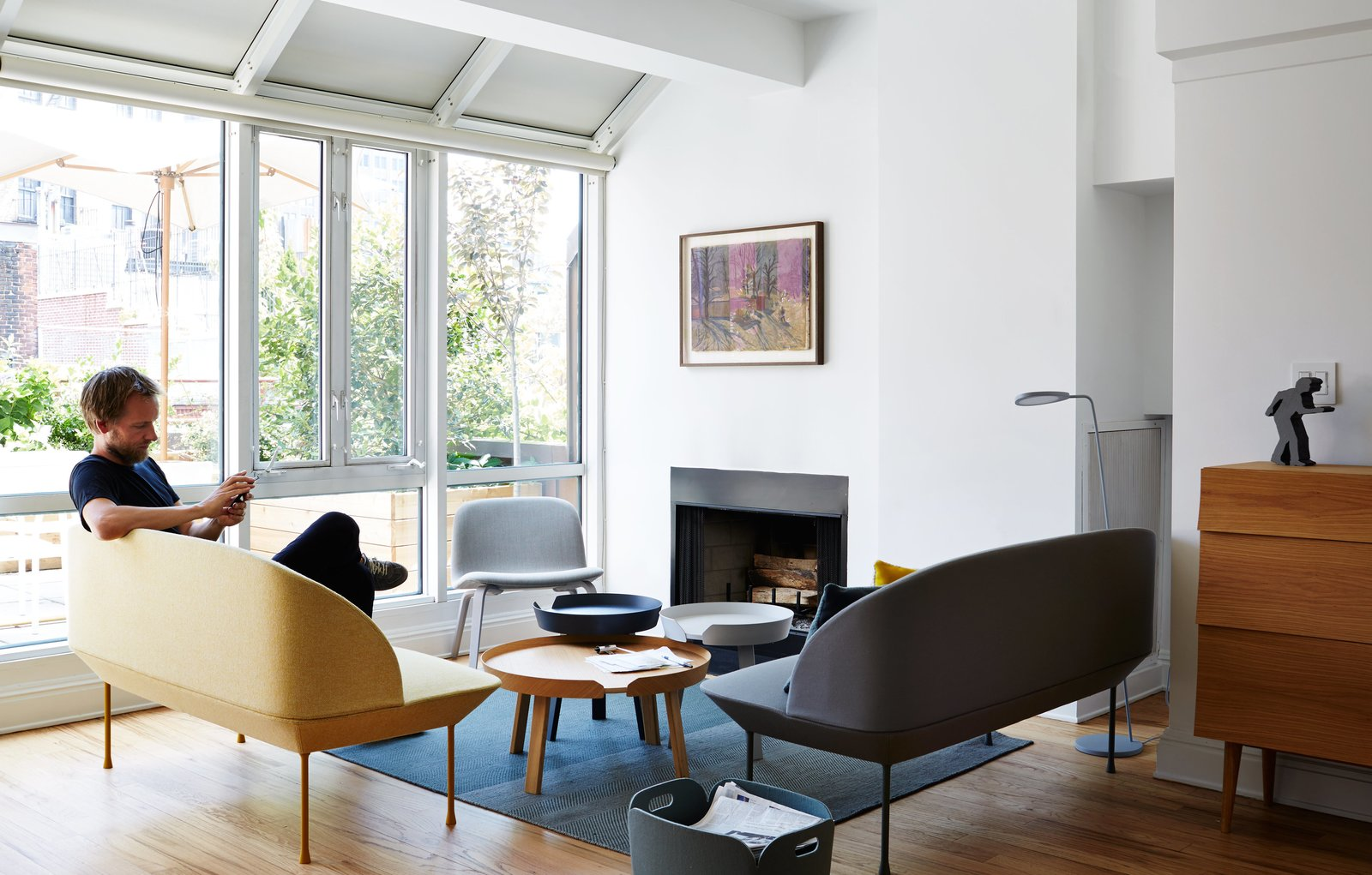 The setup around the fireplace includes a sister piece in a neutral gray, coffee tables by Thomas Bentzen, and a Visu lounge chair by Mika Tolvanen, all for Muuto.  Photo 4 of 12 in A Danish Design Kingpin Moves to NYC with a Shipping Container of Furniture in Tow