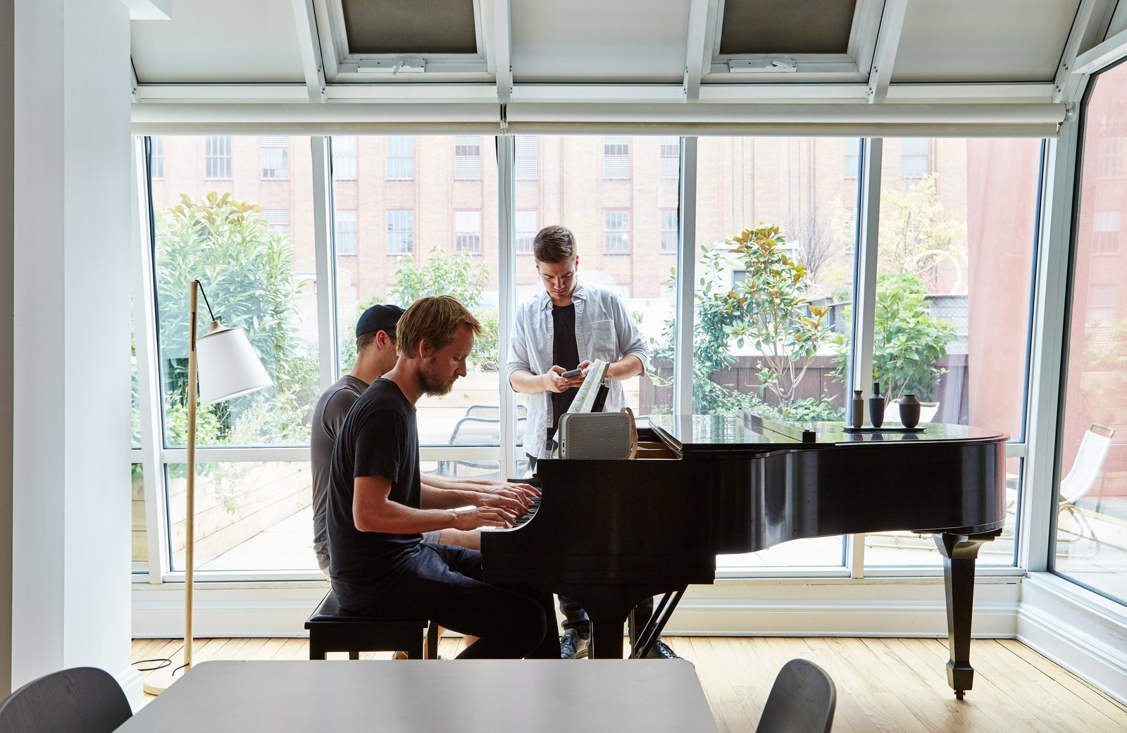 Peter and two of his U.S. colleagues gather around the Steinway piano. Tagged: Living Room and Light Hardwood Floor.  Photo 5 of 14 in A Danish Design Kingpin Moves to NYC with a Shipping Container of Furniture in Tow