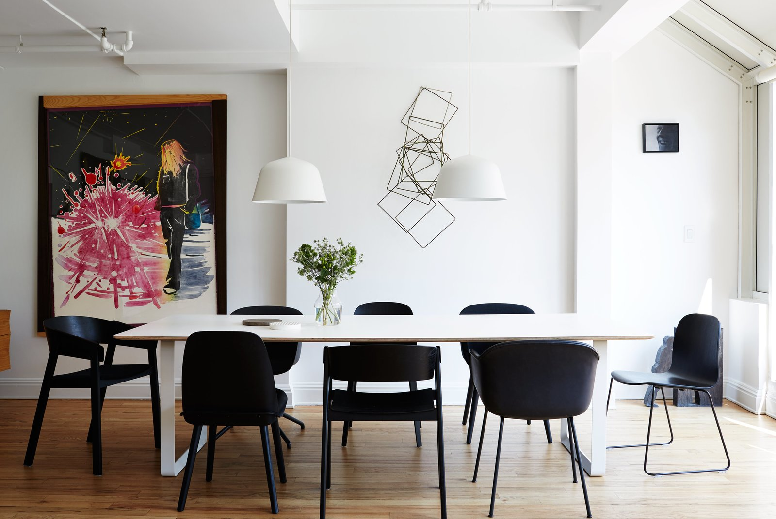 A series of black Muuto chairs—Fiber, Cover, Nerd, and Visu—surrounds a 70/70 table and white Ambit pendants, both by TAF Architects for Muuto. Tagged: Dining Room, Chair, Table, and Pendant Lighting.  Photo 6 of 14 in A Danish Design Kingpin Moves to NYC with a Shipping Container of Furniture in Tow